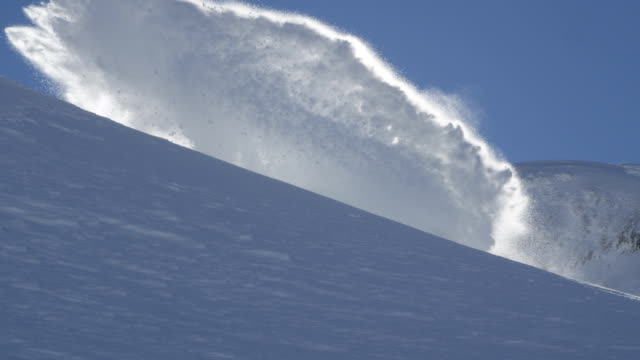 SLOW MOTION: Happy snowboarder riding powder and spraying snow over the sun video