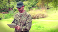 Happy soldier using tablet computer video