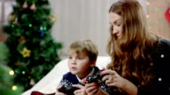 happy son and mother playing video game on playstation video