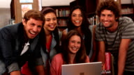 Happy students standing in the library with laptop video