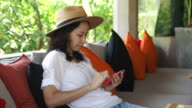 Happy summer vacation girl relaxing using smartphone in a colourful seats of tropical resort video