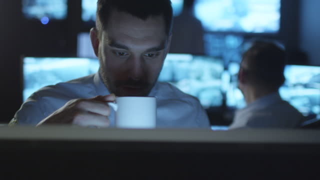 Happy technical support specialist is drinking coffee while working on a computer in a dark monitoring room filled with display screens. video