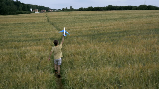 Happy teen boy playing with toy airplane against beautiful nature background, slow motion video
