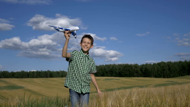 Happy teen boy playing with toy airplane against beautiful nature background video