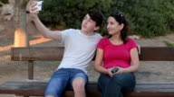 Happy teenage boy with his mother taking selfie in the park video