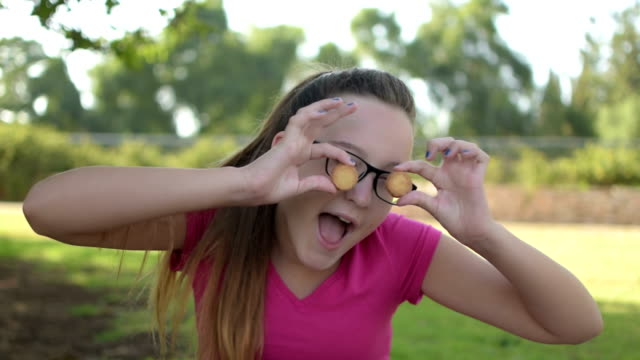 Happy teenage girl  closing her eyes with round cookies and making fun video