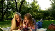 Happy Teenage girls reading a book outdoors. video