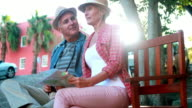 Happy tourist couple sitting on bench holding map video