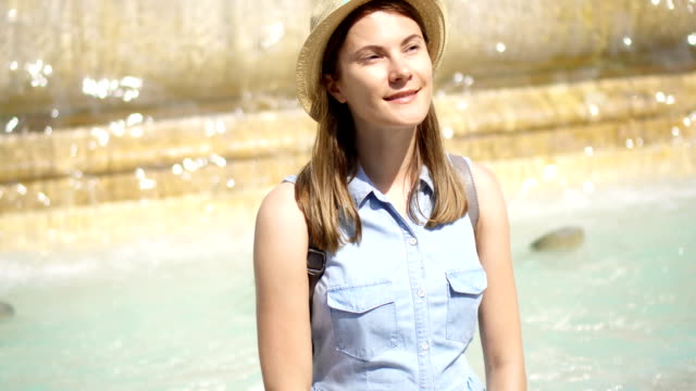 Happy tourist in hat sitting on old yellow fountain with water streaming. Girl on vacation in Europe video