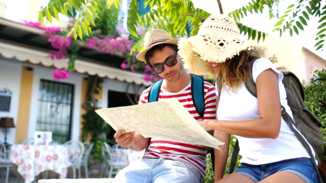 Happy tourists sightseeing city with map video