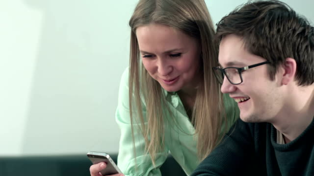 Happy two young students sitting at table and reading text message in libraly in university video