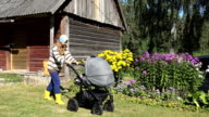 Happy villager peasant mother try to send baby to sleep in stroller buggy near rural house video
