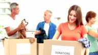 Happy volunteer family separating donations stuffs video