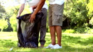 Happy volunteers picking up trash in the park video