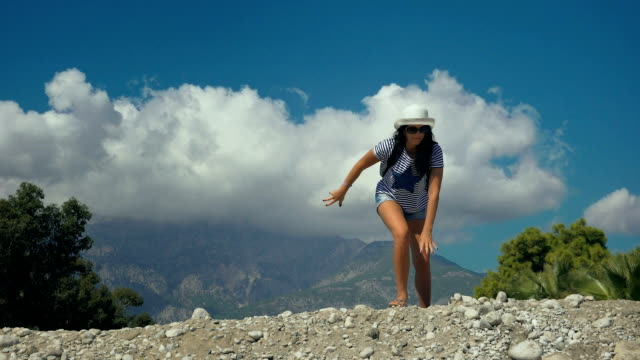 Happy woman climbing into the mountain smiling and raising her hands up. video