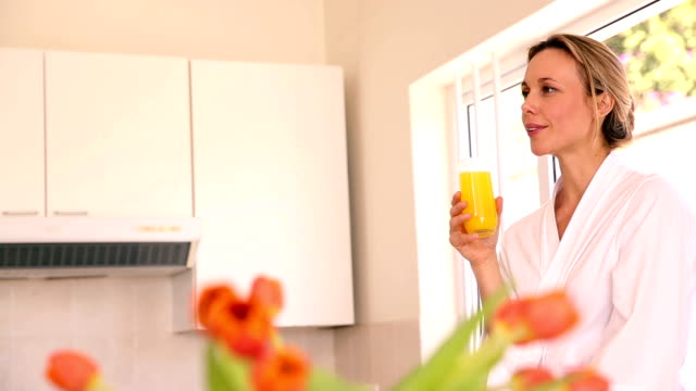 Happy woman drinking orange juice in the morning video