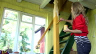 Happy woman girl with brush painting wooden pole in rural garden room. FullHD video