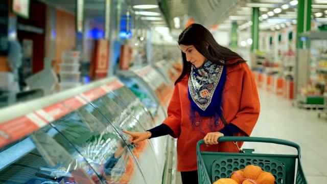 Happy woman grocery shopping at the supermarket video