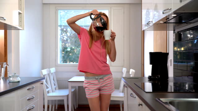 A happy woman in pajamas, dancing in the kitchen, coffee, headphones, smartphone. Dolly video