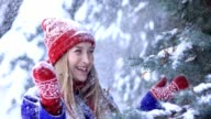 Happy woman in winter forest getting snow shower video