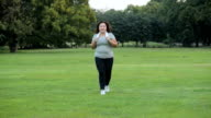 Happy woman jogging in a park video