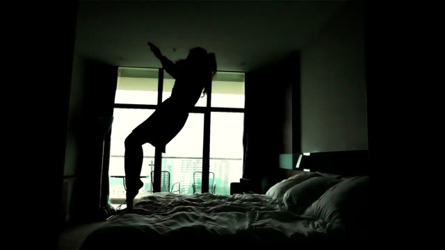 Happy woman jump on bed in luxury hotel apartment video