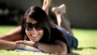 Happy woman lying on grass with digital tablet video