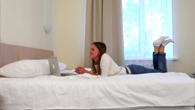 Happy woman lying on the hotel bed having video call via laptop video