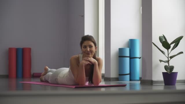 Happy  woman lying on yoga matt video