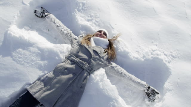 SLOW MOTION: Happy woman making snow angels on sunny day video