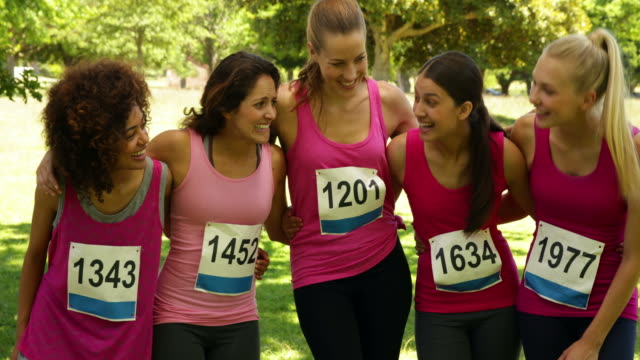 Happy woman racing pink for breast cancer awareness video