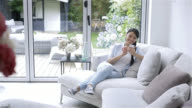 Happy woman sitting on the sofa using her smartphone video