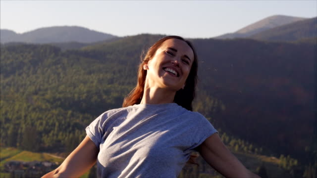 Happy woman spinning at sunset in mountains video