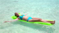 SLOW MOTION: Happy woman sun tanning on inflatable airbed mattress video
