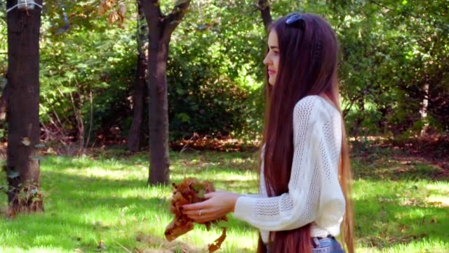 Happy woman throwing leaves in Autumn park in slow motion, smiling video