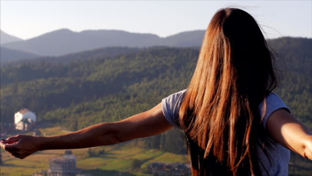 Happy woman whirling at sunset in mountains video