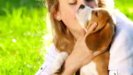 happy woman with a dog beagle playing on nature video