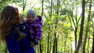 happy woman with baby girl in arms walk in autumnal park. FullHD video