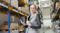 Happy woman with tablet in warehouse video