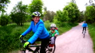 Happy Woman With Two Children Cycling In Green Park video