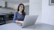Happy woman working from home using her laptop video
