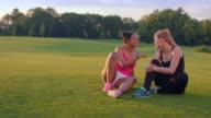 Happy women sitting on grass in summer park. DIverse friends talking outdoors video