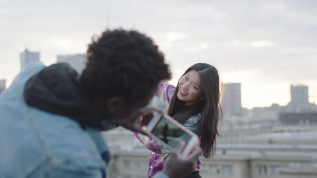Happy young asian woman posing on roof to photographer with smartphone video