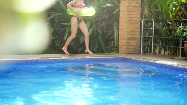 Happy young beautiful woman with an inflatable circle runs into the swimming pool in slow motion. 1920x1080 video