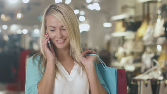 Happy young blond girl is standing in a department store and talking on the phone. video