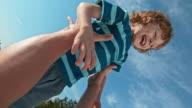SLO MO Smiling boy being tossed into air in sunshine video