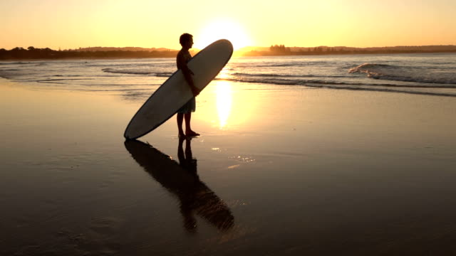 SLOW MOTION: Happy young boy standing on sandy beach and holding longboard video