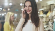 Happy young brunette female is standing in a department store and talking on the phone. video