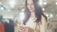 Happy young brunette girl is standing in a department store and texting a message on a smartphone. video