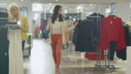 Happy young brunette girl is walking though a clothing store in orange trousers. video